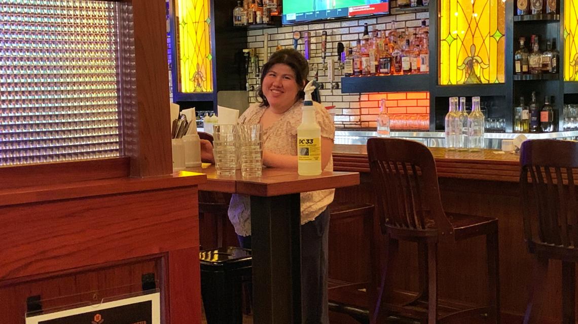 Erika smiling at the camera while working at Tavern Hall.